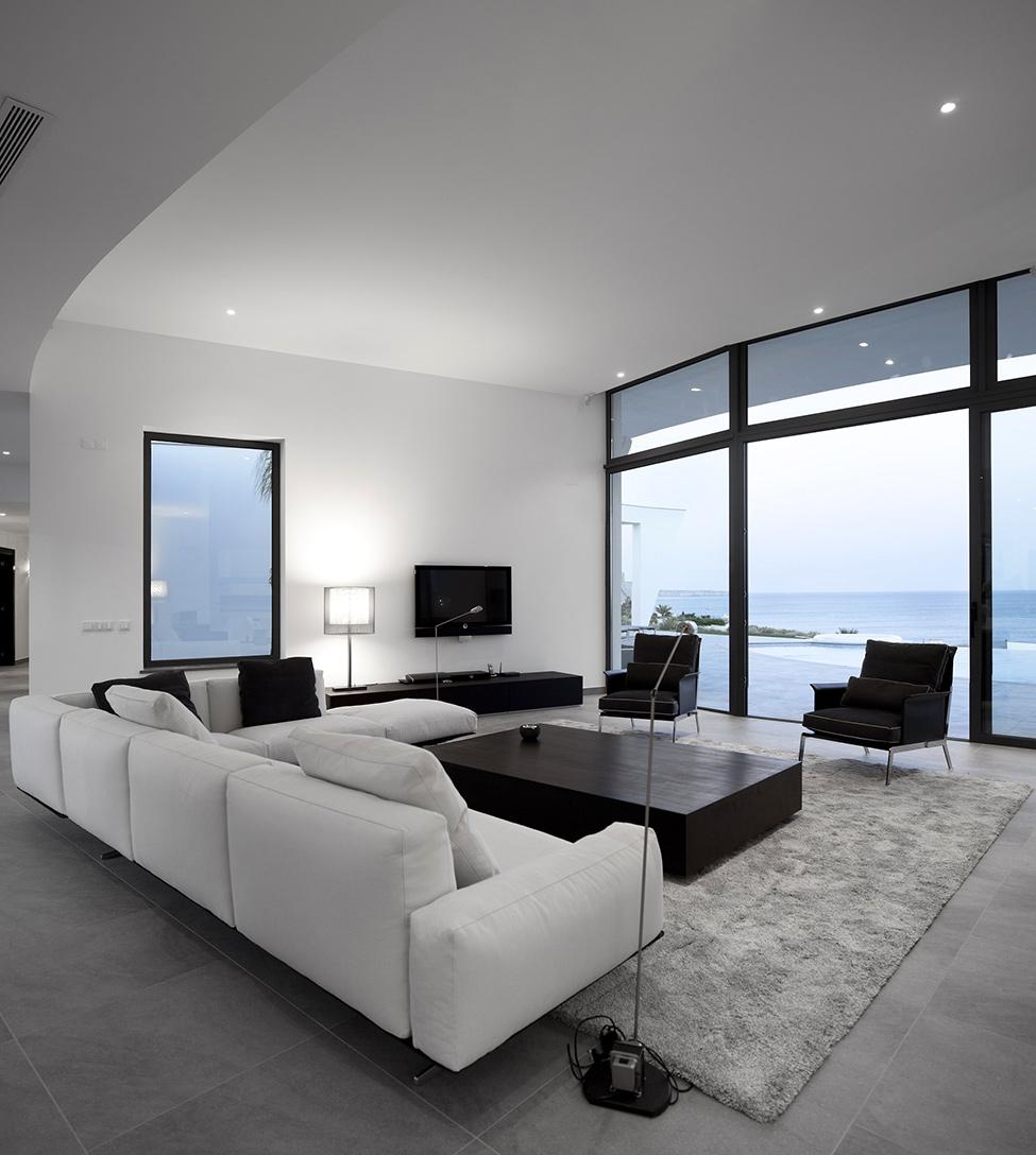 这座新概念别墅位于葡萄牙阿尔加维拉各斯镇海滩边,由本土建筑师Mario Martins设计完成。别墅外观呈白色,拥有优美的弧线外形,两端的屋角高高地翘起,房屋则被包围在弧形墙体之下,粗犷中透露着优雅与时尚。游泳池则位于房屋弯曲的中心部位,并与不远处的大海连成一片。室内以黑白两色为主,简约装饰风格,宽大的落地玻璃窗确保了室内的采光,并使房屋拥有更为宽广的视野,可以欣赏壮美的海景